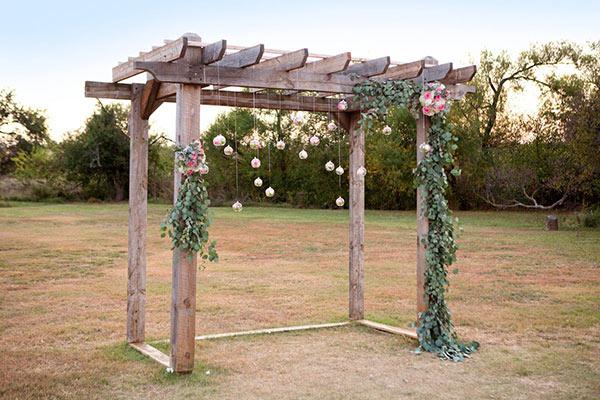 Pergolado de eucalipto decorado com plantas.