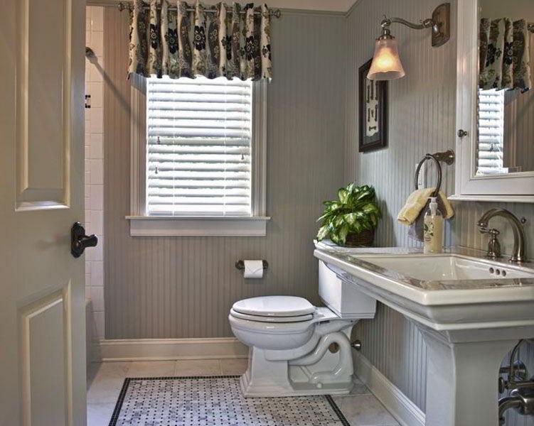 Banheiro pequeno com janela de madeira.
