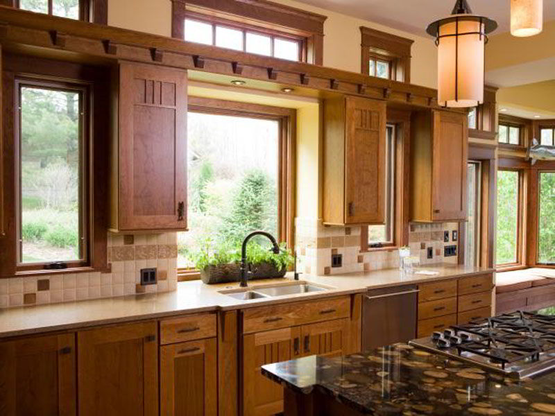 Cozinha com muitos detalhes em madeira no mesmo tom da janela de madeira.