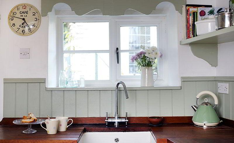 Cozinha com janela de madeira pequena e branca.