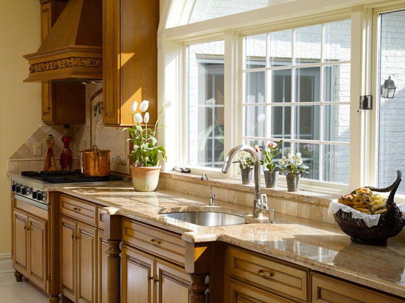 Cozinha com janela de madeira branca em tom diferente dos outros móveis.