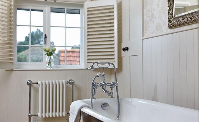 Janela de madeira branca combinando com a decoração clean do banheiro.
