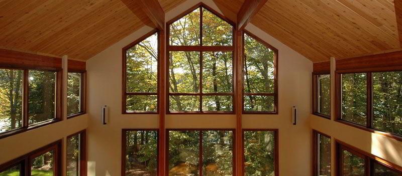 Aqui a janela de madeira com vidro combina com o teto de madeira.