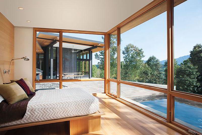 Visual incrível de quarto com janela de madeira e vidro que substitui as paredes!