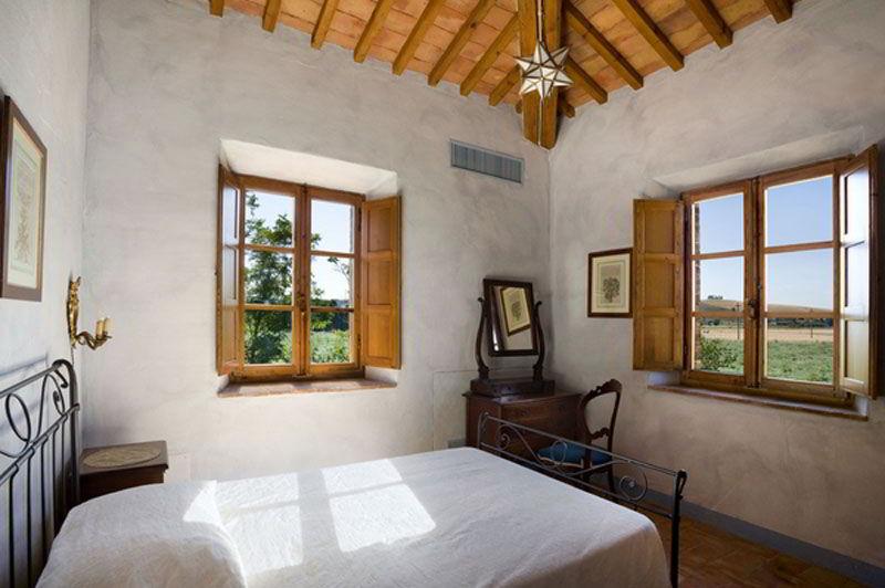 Quarto com decoração simples que combina a madeira da janela com a do teto.