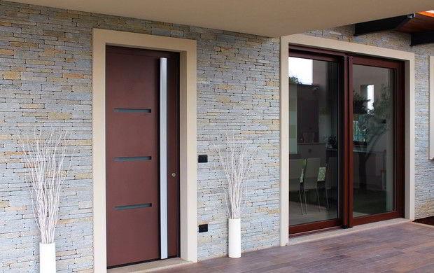 Porta de madeira com vidro e puxador metálico em ambiente urbano e luxuoso.