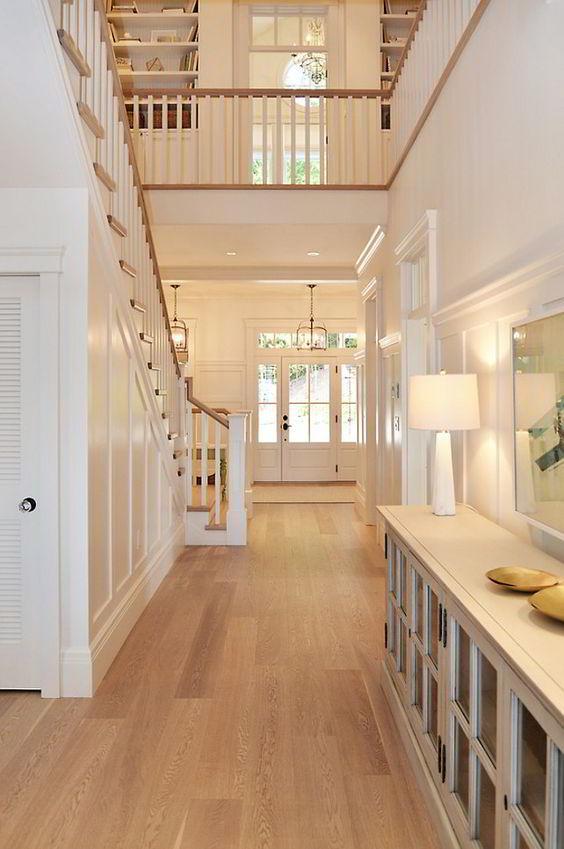 Piso de carvalho branco combinando com a sofisticação de um hall em tons claros.