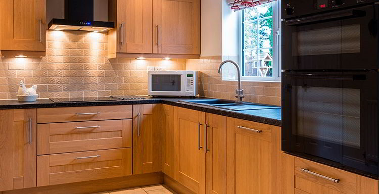 Cozinha com móveis de madeira cerejeira.