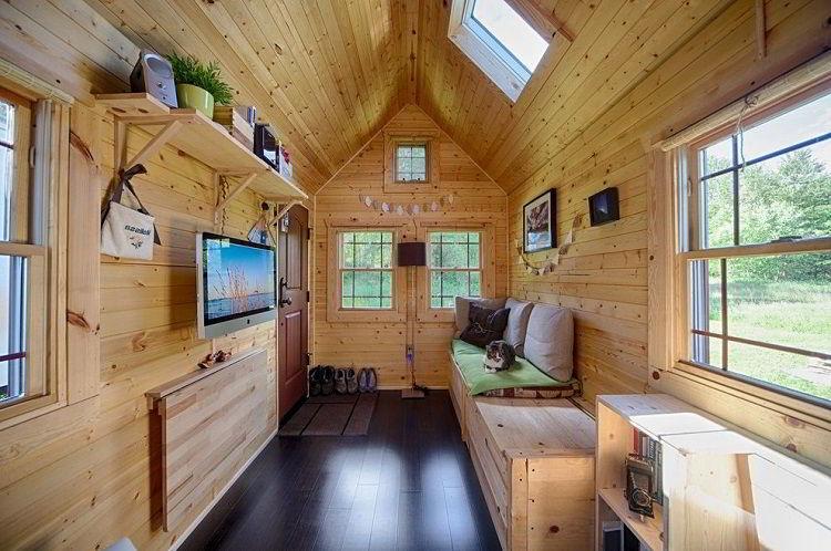 Sala de estar pequena com paredes e teto revestidos de pinus.