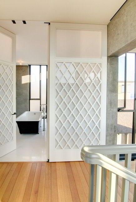 Porta de banheiro com treliça d emadeira branca.