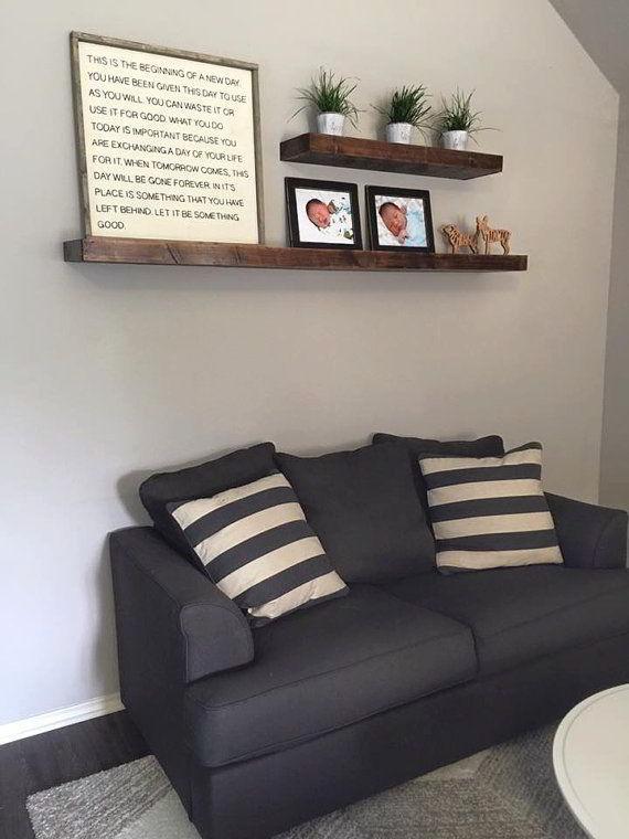 Prateleiras de madeira tradicionais instaladas acima do sofá da sala.