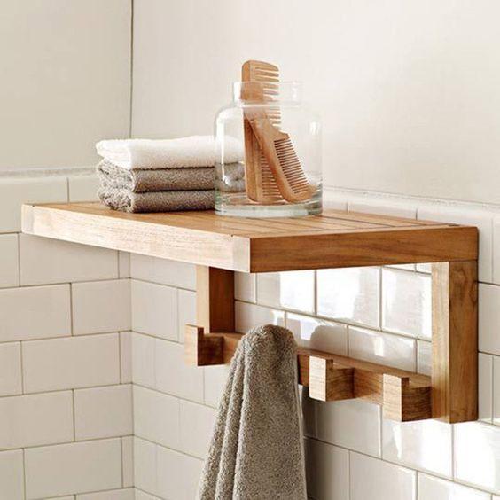 Prateleira de madeira com suporte para toalha.