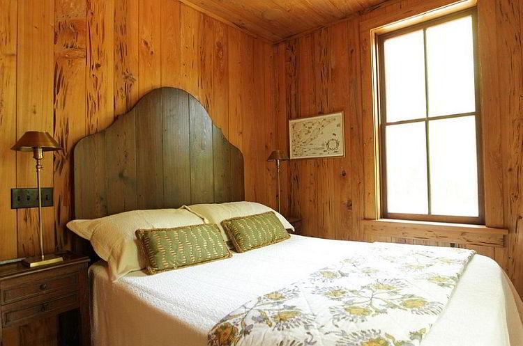 Cama com cabeceira de madeira simples em quarto de estilo rústico.