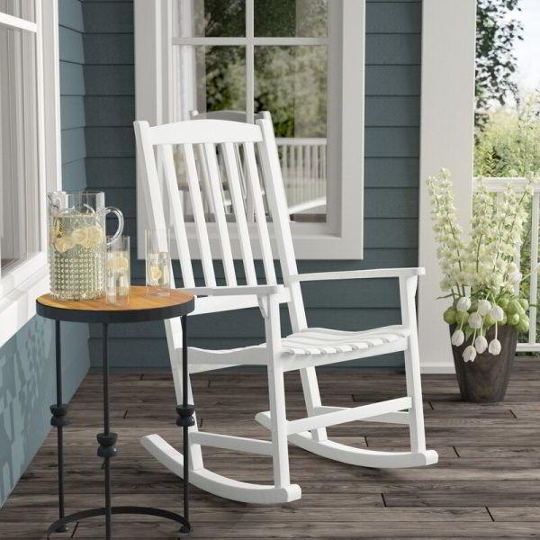Cadeira de balanço de madeira branca ripada numa varanda.