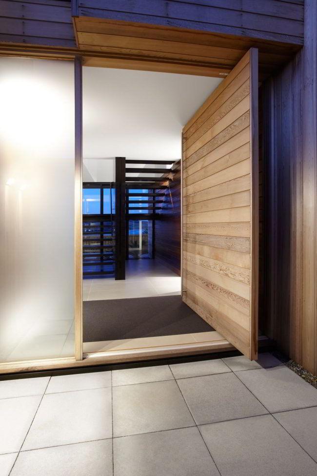 Porta de madeira pivotante grande com vidro opaco à esquerda.