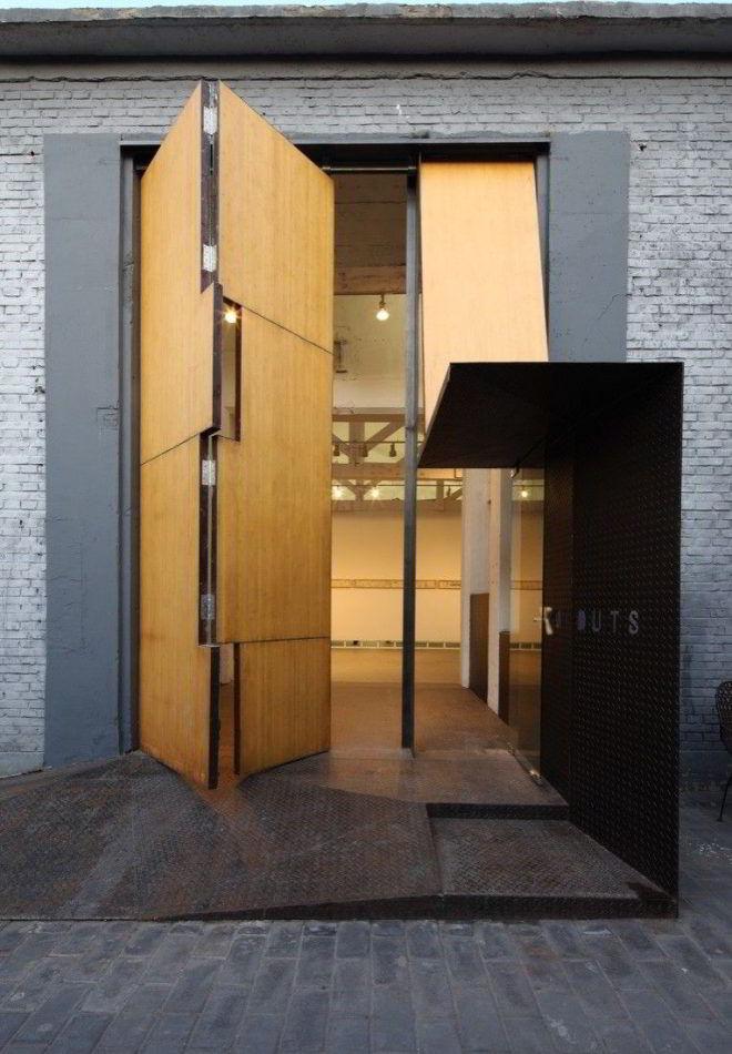 Porta pivotante de madeira enorme na entrada de um espaço cultural.