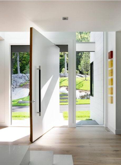 Porta pivotante de madeira branca em espaço clean e sofisticado.