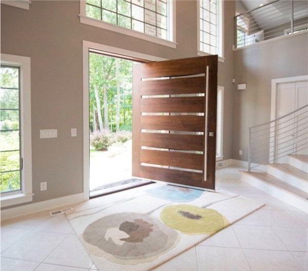 Porta de madeira pivotante com tiras de vidro para entrar luz.