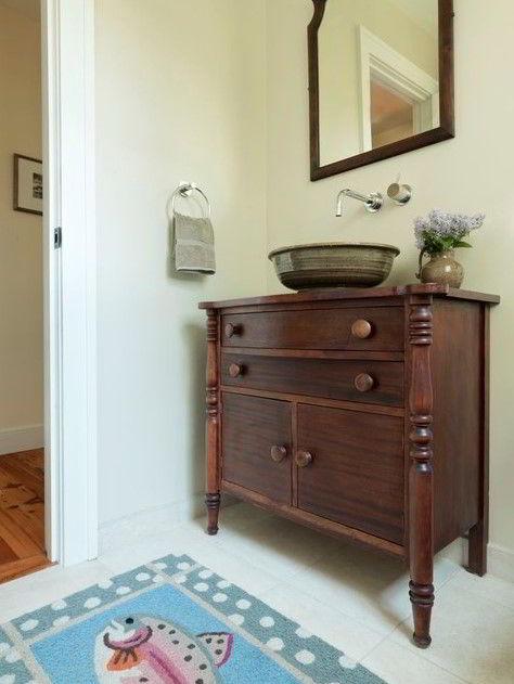Cômoda antiga de madeira marrom escuro restaurada como suporte de pia de banheiro.