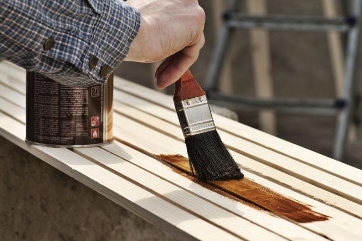 Verniz com cor escura sendo aplicado em madeira clara.