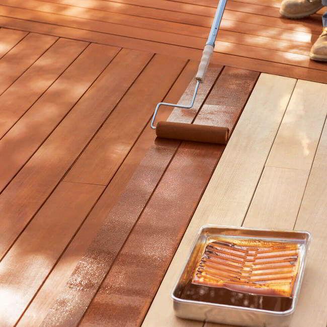 Deck de madeira amarela sendo pintado com verniz com cor castanha.