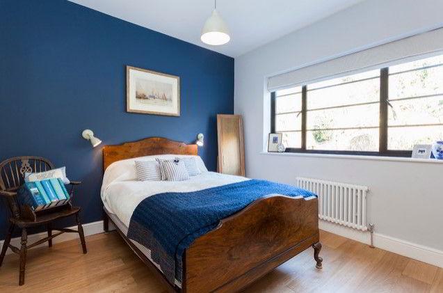 Quarto com cama e piso de madeira escura com objetos na tonalidade azul, garantindo equilíbrio ao ambiente.