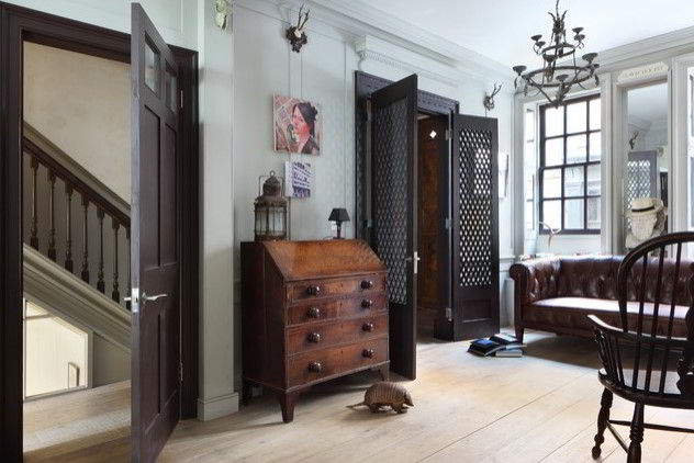 Cômoda e cadeira de madeira escura combinados com outros objetos de tons escuros.