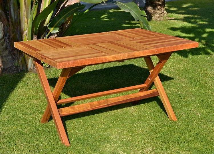 Mesa de madeira dobrável de cor clara no jardim.
