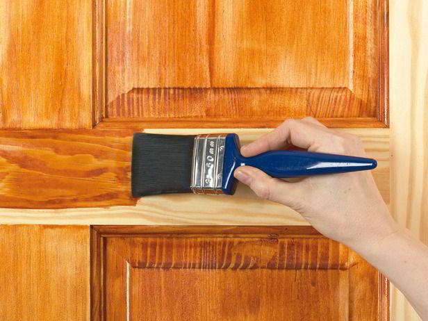 Porta de madeira recebendo verniz com pincel.