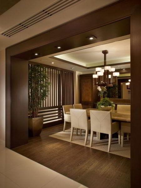 Grande batente de madeira escura com iluminação na entrada da sala de jantar elegante.