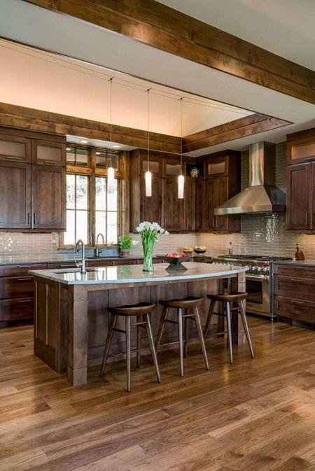 Ilha e armários de madeira castanha em cozinha rústica.