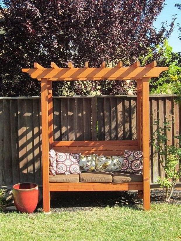 Banco de madeira com pergolado e almofadas no jardim