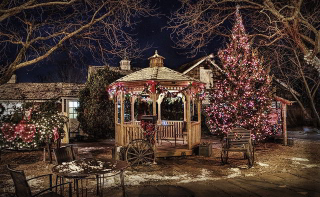 Quiosque de madeira em jardim enfeitado para o Natal.
