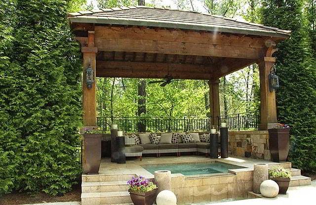 Cabana de madeira em jardim com jacuzzi e sofás.