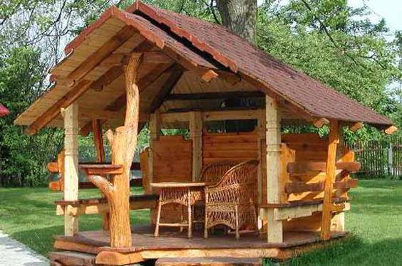 Gazebo com parede de madeira e cadeiras de vime.