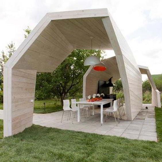 Quiosque de madeira clara grande em jardim.