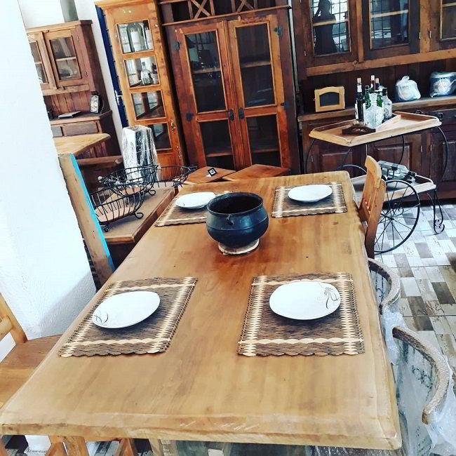 Mesa de jantar de madeira pequi combinando com o resto da decoração em madeira.