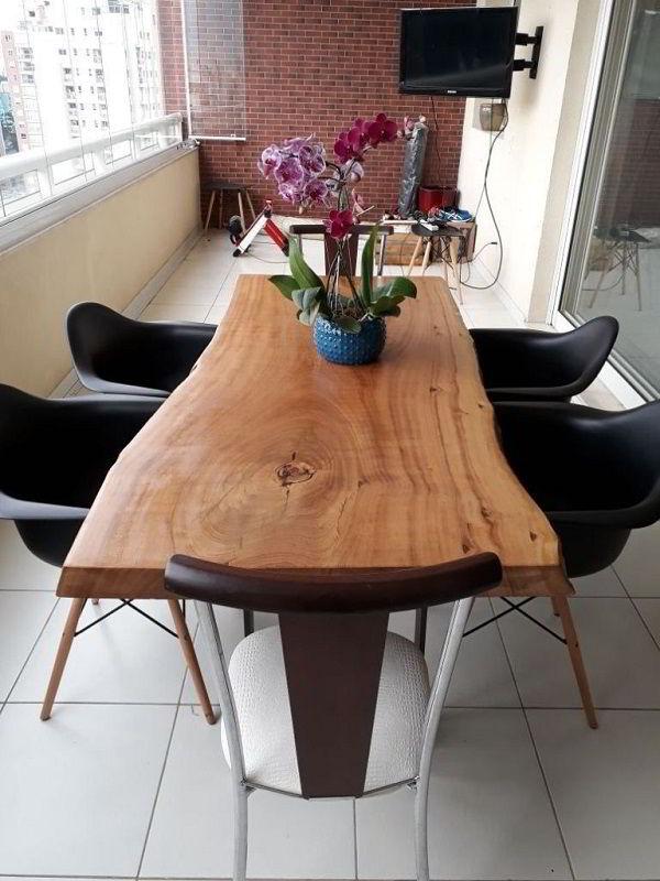Mesa de jantar de madeira pequiá no estilo rústico com vaso de flores no centro.
