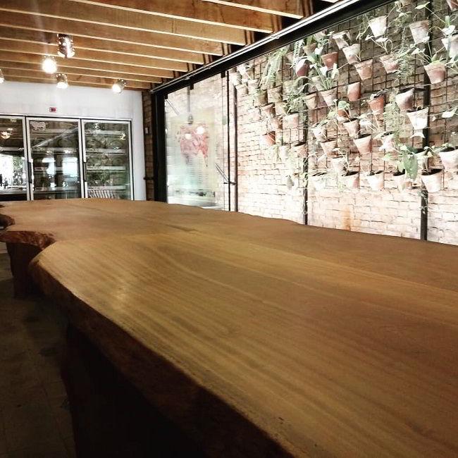 Mesa bem grande madeira piquiá combinando com vigas de madeira no teto.
