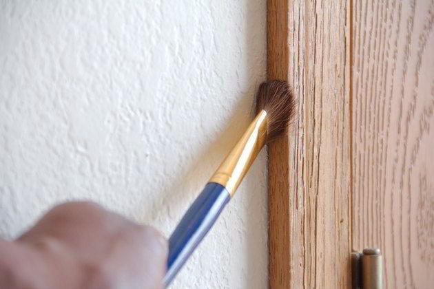 Um pincel pode ajudar a limpar cantinhos da porta de madeira.