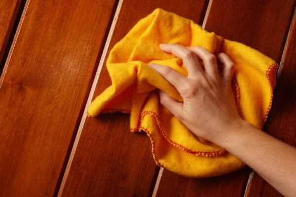 Termine a limpeza da porta de madeira polindo com um lustra-móveis.