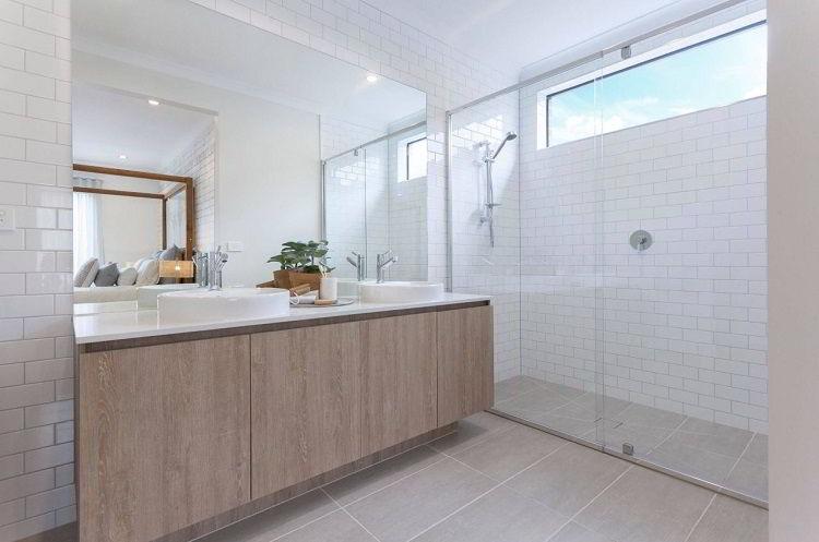 Balcão de banheiro em madeira clara combinando com pias brancas.