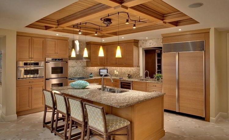 Cozinha com balcão, cadeiras, armários e teto de madeira em cor clara.