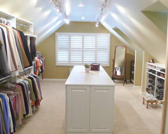 Closet walk-in com prateleiras e ilha de madeira branca.