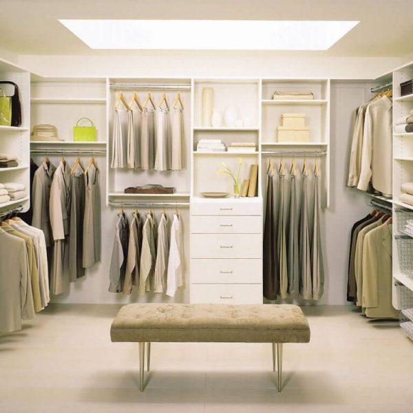 Closet de madeira branca com banco no meio do quarto.