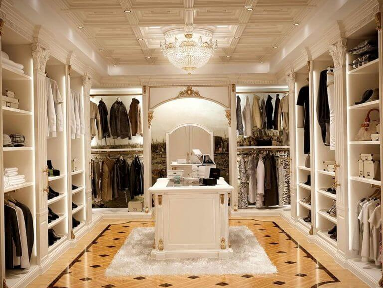 Closet luxuosíssimo com madeira branca, ilha e lustre.