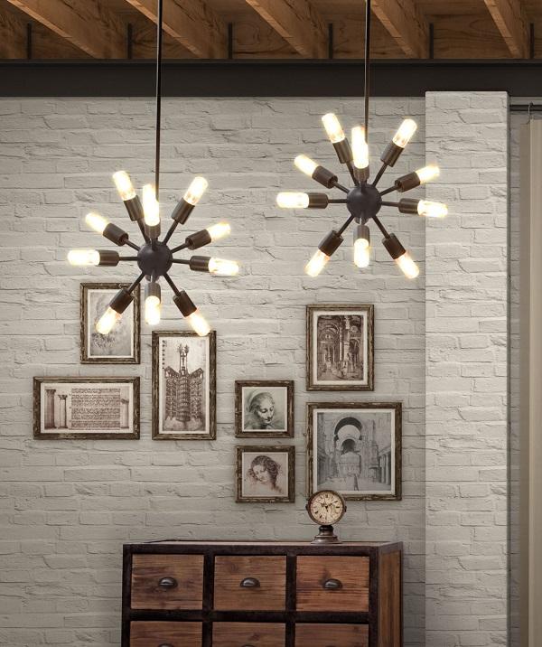 Duas estruturas de luminárias penduradas no teto com várias lâmpadas que formam um asterisco.