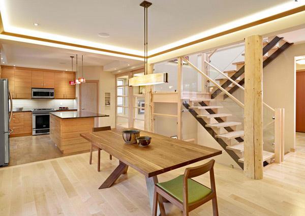 Sala de jantar de madeira em vários pontos do cômodo: mesa, escada, piso, balcão e armários.