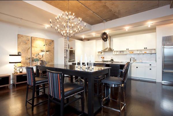 Bela sala de jantar em design diferenciado com mesa de madeira preta e bancos altos.