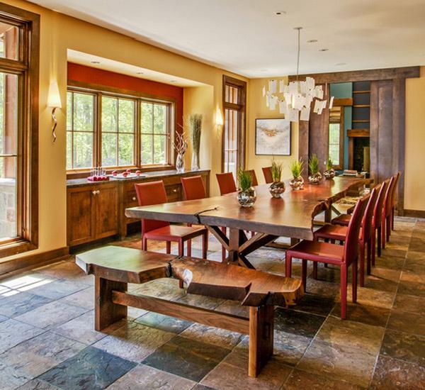 Mesa de jantar grande de madeira com cortes irregulares e banco rústico.